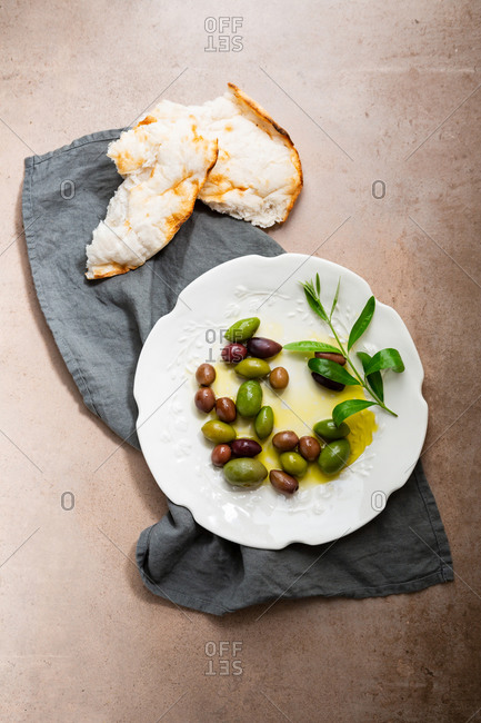 Pickled olives on plate and flat bread