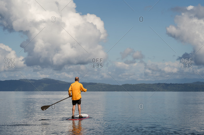 Rear view of middle aged man on a stand up paddleboard