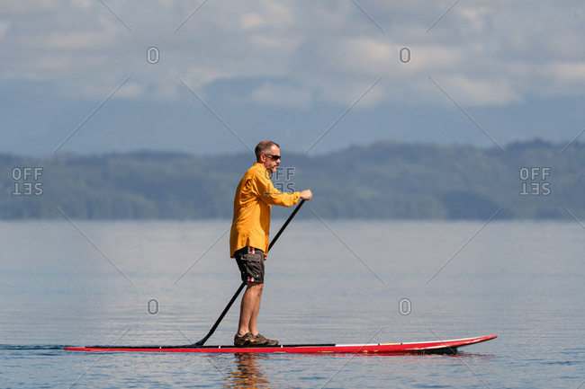 Middle aged man on a stand up paddleboard in the ocean