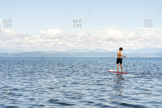Teenage on a paddleboard on the ocean