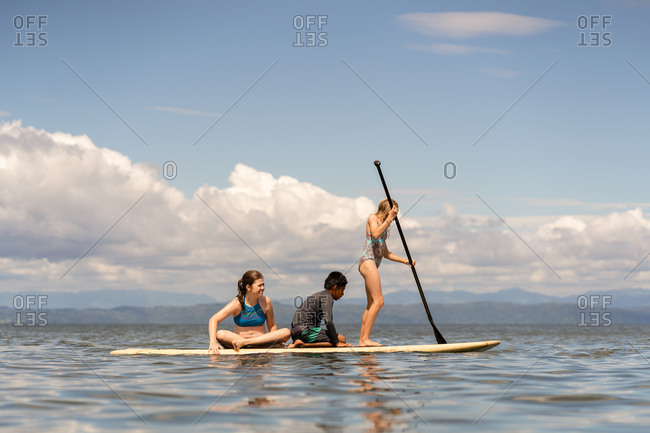 Three people on a stand up paddleboard