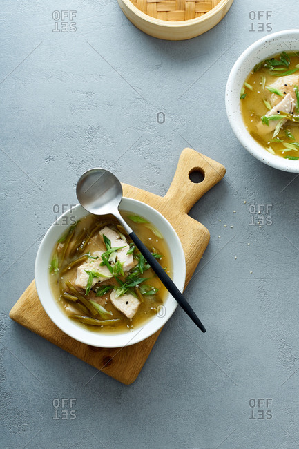 Miso soup with green beans and chicken on gray concrete background