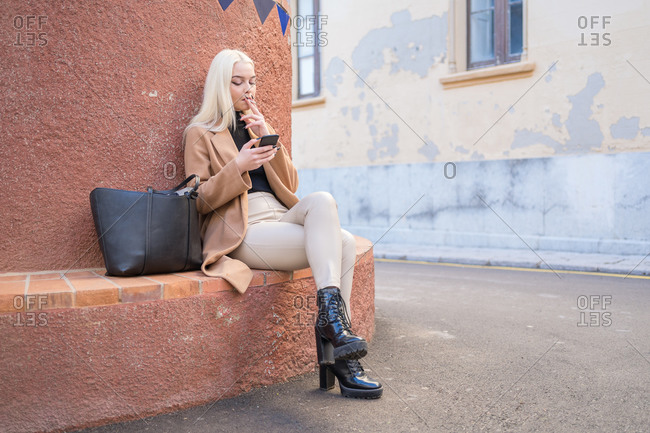 Blonde woman sits on ledge and smokes