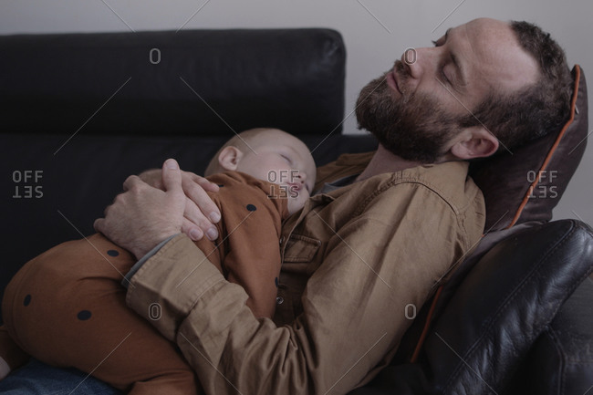 Single Father and baby sleeping on sofa in living room
