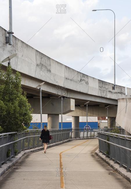 March 29, 2020:Woman walking in Brisbane between bridges and roads