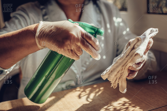 Close up of a person spraying disinfectant on a rag while wearing safety gloves