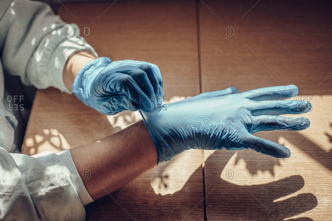Close-up of a woman's hands putting on latex gloves