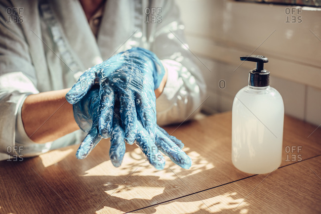 Close-up of a woman's hands pouring disinfectant soap on her hands wearing gloves