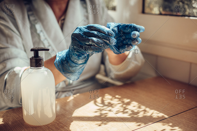 Close-up of a woman's hands taking off latex gloves