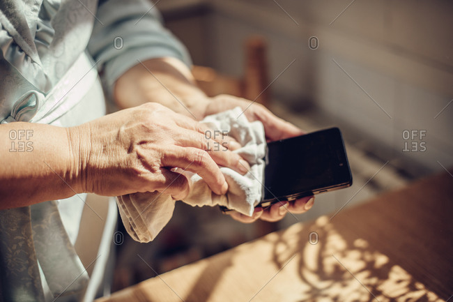 Close up of a woman's hands spraying disinfectant on a cell phone