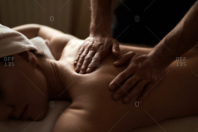 Woman laying on massage table receiving back massage