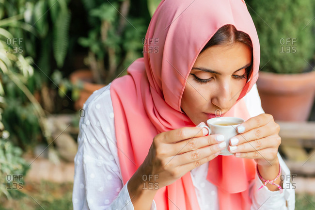 Portrait of a beautiful young Muslim woman with pink hijab drinking English tea in a garden cafe