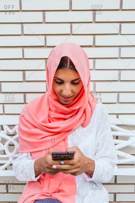 Portrait of a beautiful young Muslim woman with pink hijab typing on a smartphone while sitting on a bench with white brick background