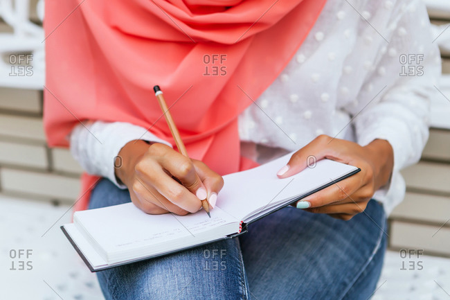 Close up of a unrecognizable young Muslim woman with pink hijab writing on a notebook with white brick background