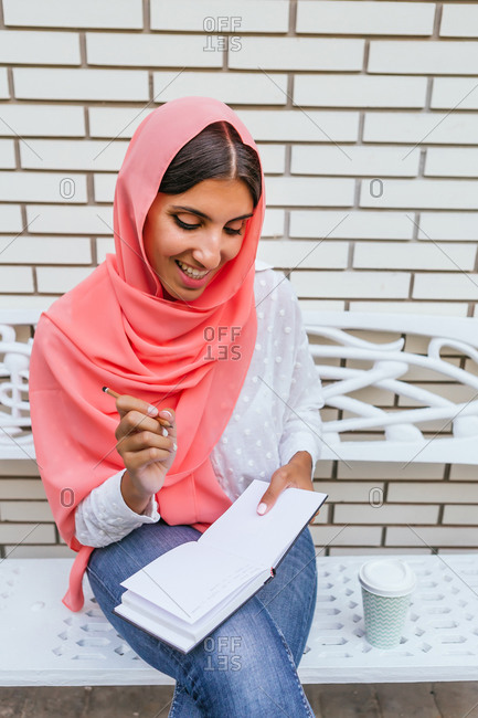 Portrait of a beautiful young Muslim woman with pink hijab smiling and writing on a notebook with white brick background