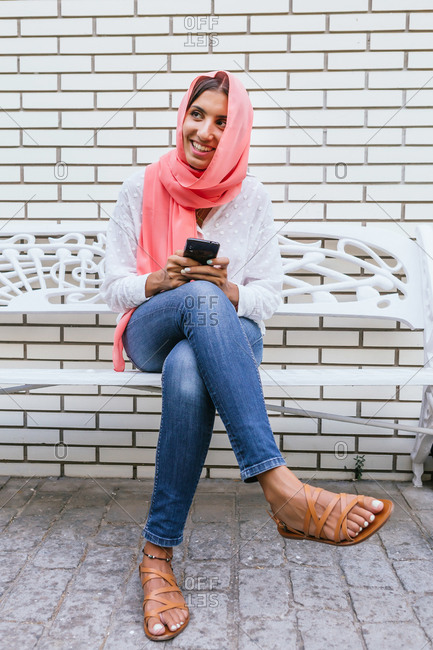 Portrait of a beautiful young Muslim woman with pink hijab smiling and typing on a smartphone while sitting on a bench with white brick background