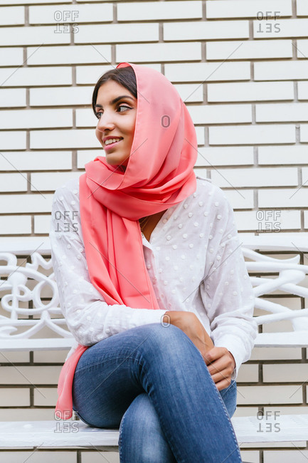 Portrait of a beautiful young Muslim woman with pink hijab smiling ad sitting in a bench with white brick background