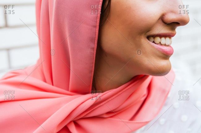 Close up of a beautiful and unrecognizable young Muslim woman with pink hijab smiling with white brick background