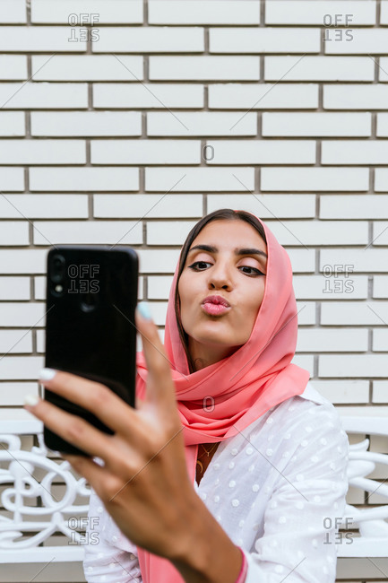 Portrait of a beautiful young Muslim woman with pink hijab kissing and taking a selfie with white brick background
