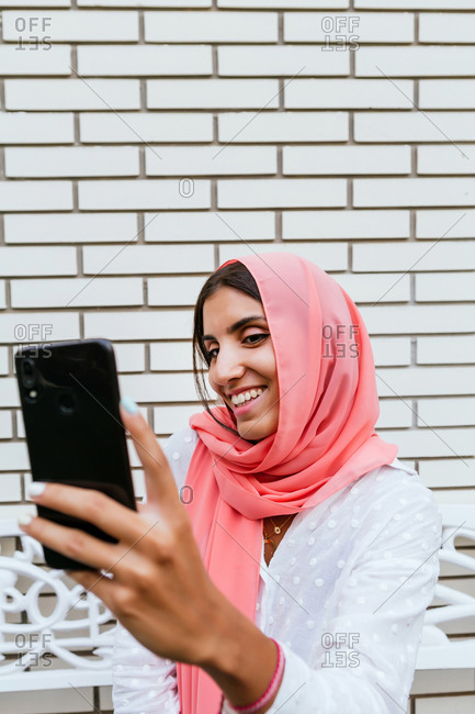 Portrait of a beautiful young Muslim woman with pink hijab smiling and taking a selfie with white brick background