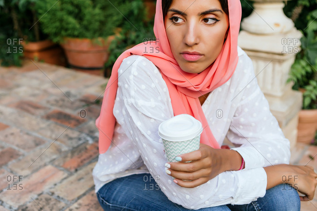 Portrait of a beautiful young Muslim woman with pink hijab drinking take-away coffee in a garden
