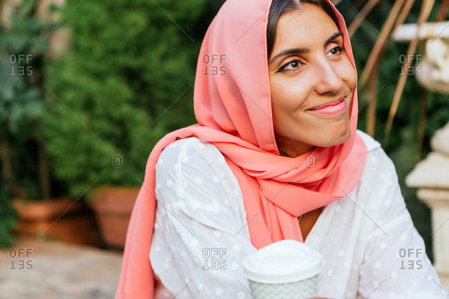 Portrait of a beautiful young Muslim woman with pink hijab smiling and drinking take-away coffee in a garden