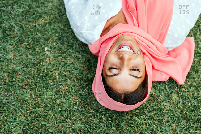 Portrait of a beautiful young Muslim woman with pink hijab lying on her back and smiling on the green grass