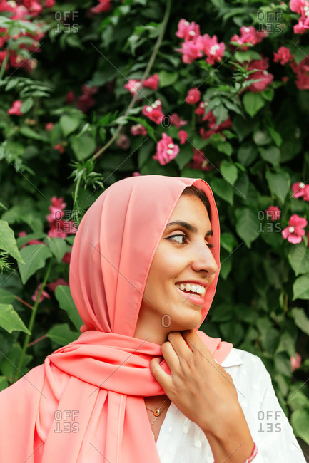 Portrait of a beautiful young Muslim woman with pink hijab smiling with flowers and plants behind her in a garden