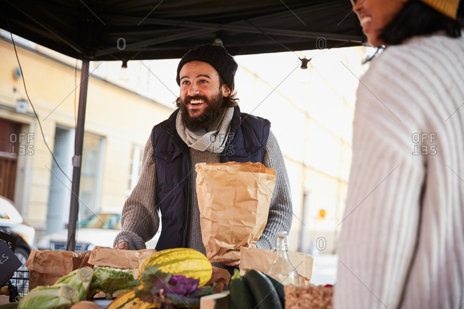 Smiling man buying vegetables from female vendor at market stall