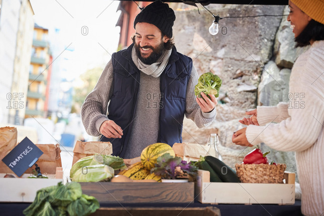 Smiling man buying fresh broccoli from female market vendor at vegetable stall