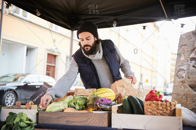 Male vendor arranging vegetables while standing at market stall