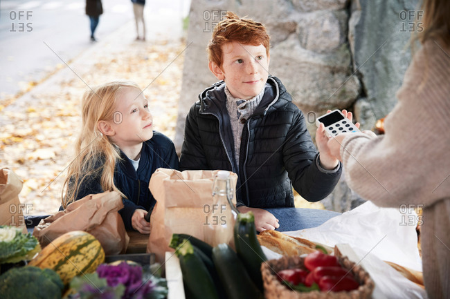 Male and female sibling with credit card reader at market stall