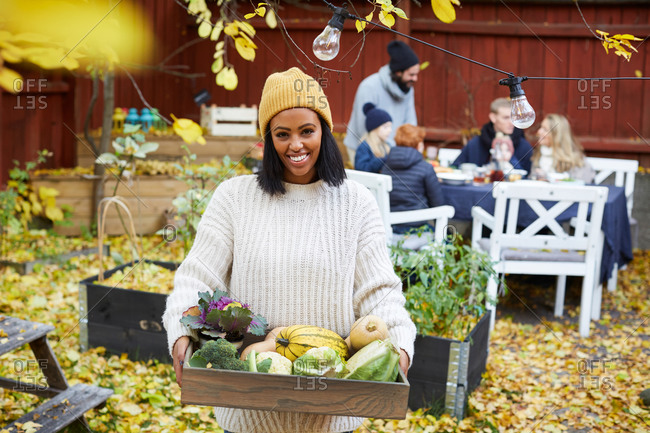 Portrait of happy woman standing with vegetable basket while family and friends sitting at table in yard