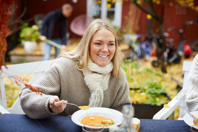 Happy female with vegetarian soup sitting by table at yard
