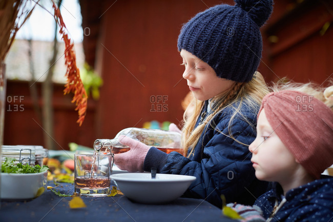Girl pouring drink in glass while sitting by female sibling at table