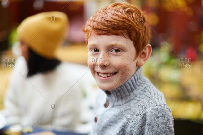 Portrait of smiling boy sitting at yard