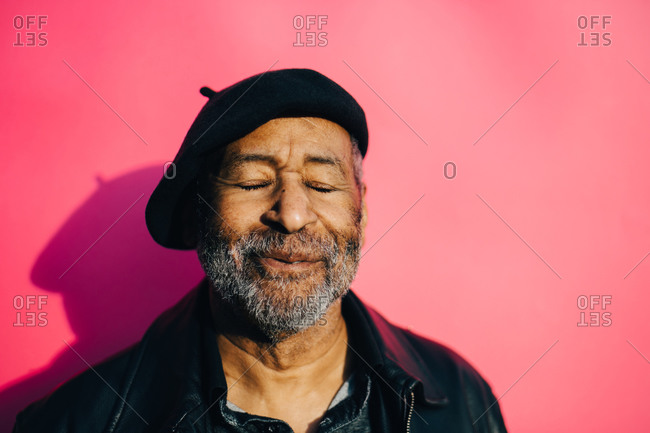 Smiling senior man with eyes closed against pink background