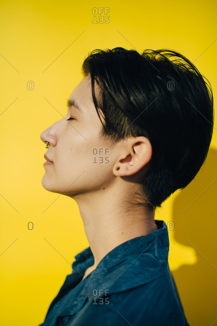 Side view of young woman against yellow background
