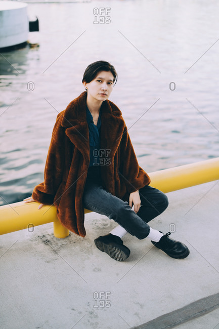Full length of young woman sitting against lake