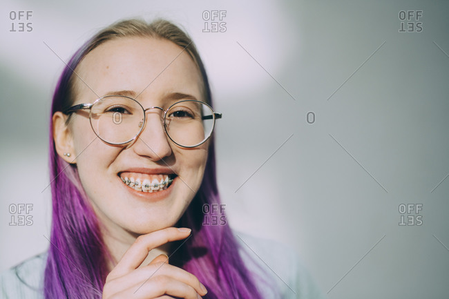 Portrait of smiling teenage girl with braces standing against wall
