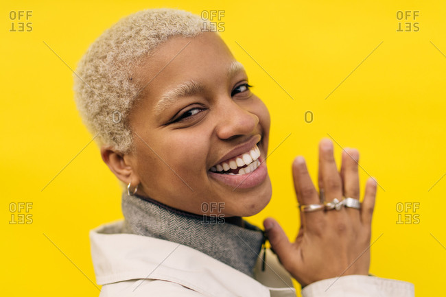 Portrait of smiling young female standing against yellow background