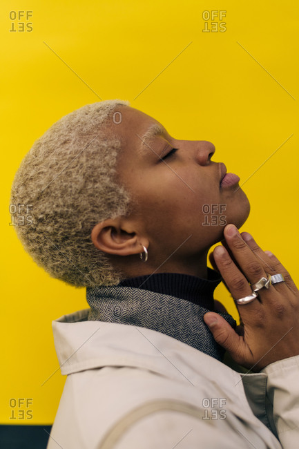 Side view of contemplating young female with eyes closed standing against yellow background