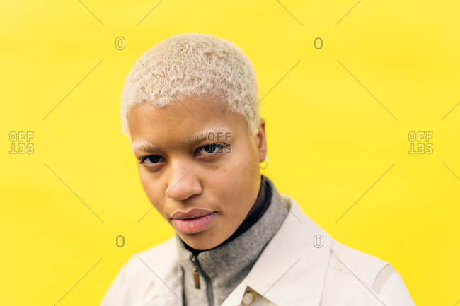 Portrait of contemplating young female standing against yellow background