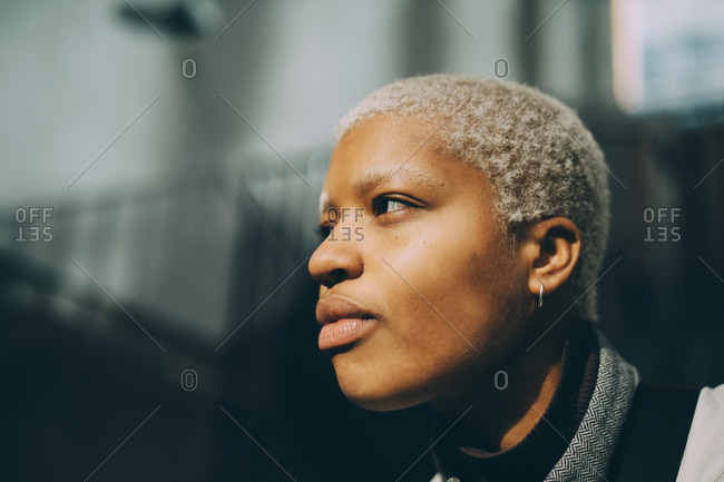 Confident young woman looking away against railing