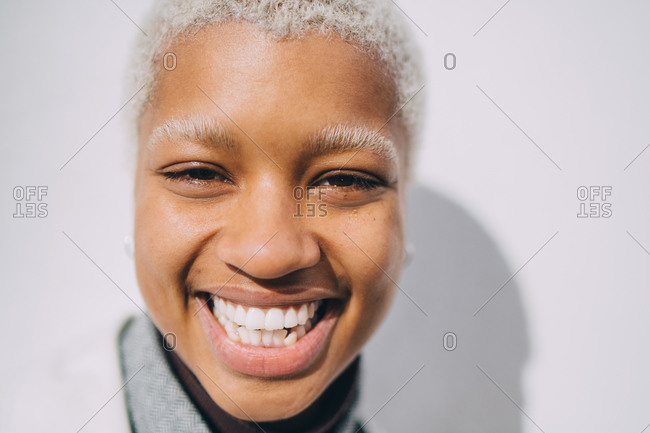 Portrait of smiling young female standing against wall
