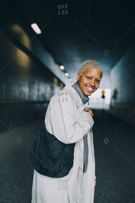 Portrait of happy young female with bag standing in corridor