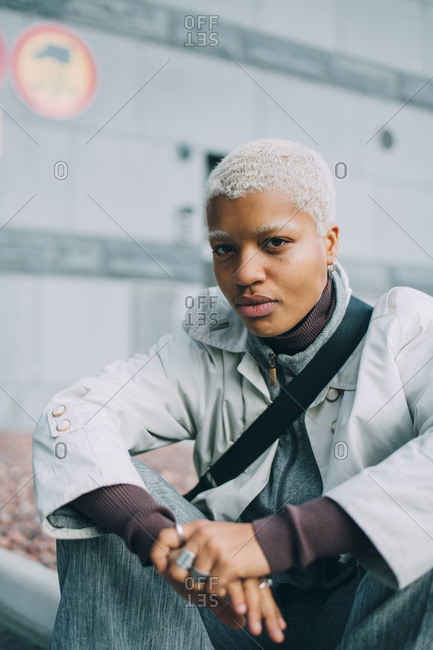 Portrait of confident young woman sitting against wall