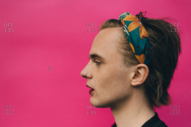Side view of confident young man standing against pink background