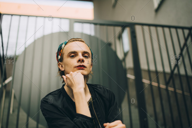 Low angle portrait of young man sitting against railing