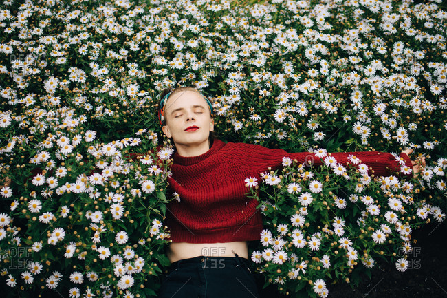 Contemplating man wearing red lipstick sleeping amidst daisy flowering plants